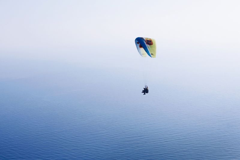 Paragliding Over Sea And Against Clear Sky