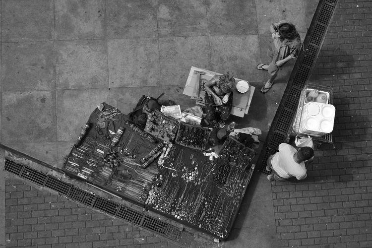 Directly above shot of female vendor selling necklaces on sidewalk