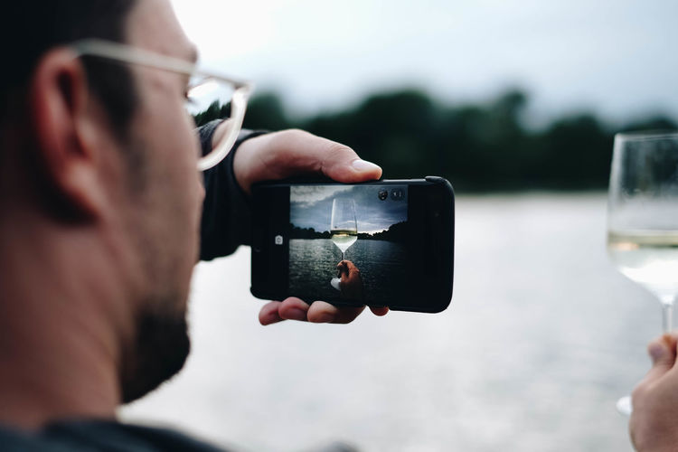 Man photographing wineglass through mobile phone