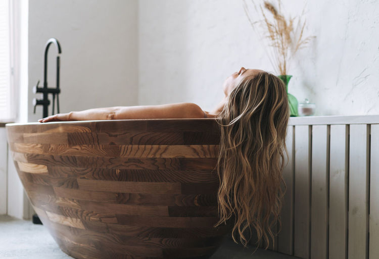 Blonde sensual young woman with long hair takes wooden bath relax at modern bathroom