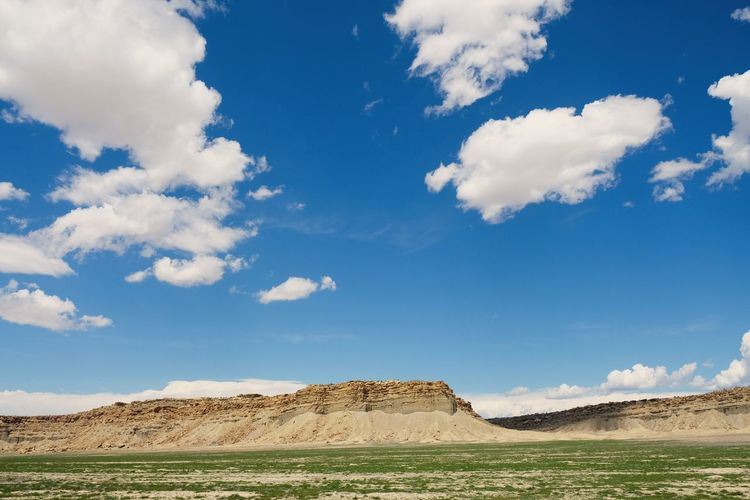 Scenic view of land against cloudy sky