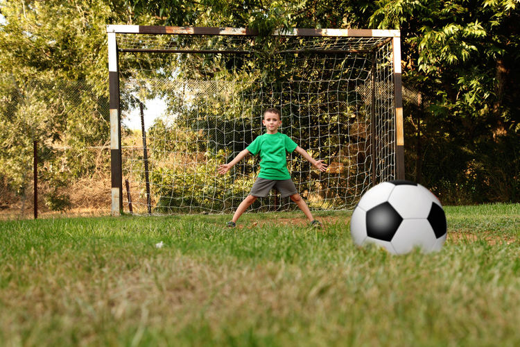 Child boy playing football in park. Active Active Lifestyle  Ball Boy Candid Child Childhood Field Football Football Field Garden Grass Grass Kid Leisure Activity Lifestyle Lifestyles Park Playground Playing Soccer Sport Summer Vacation