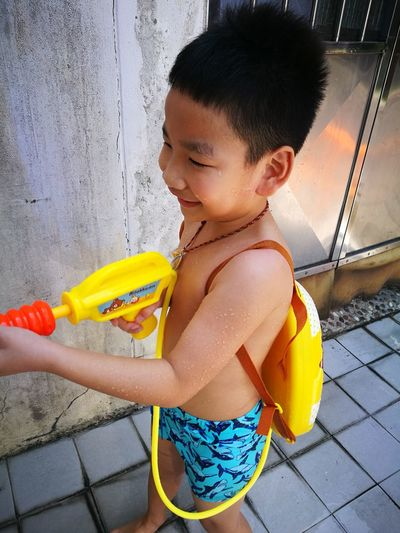High Angle View Of Shirtless Boy Standing With Squirt Gun