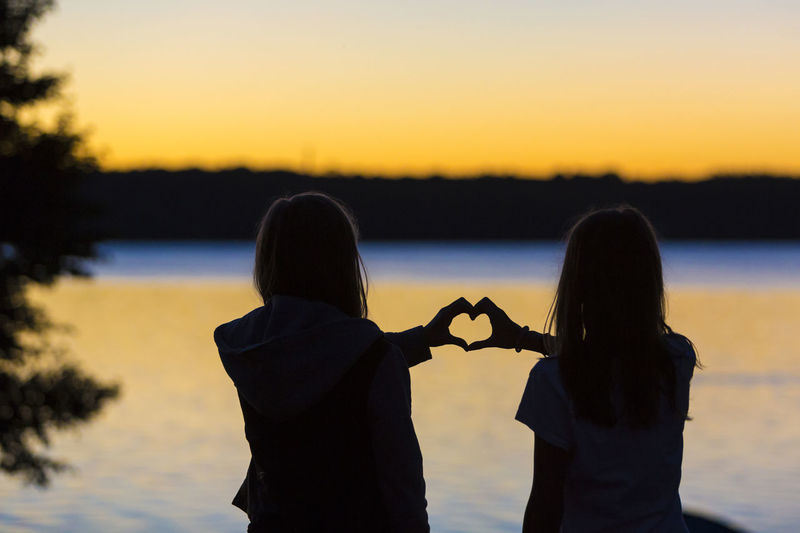 Two girlfriends forming heart sign on sunset at a lake Bavaria Chiemsee Conceptual Finger Forming Germany Girlfriend Girlfriends Heart Holiday Lake Lesbian Lesbians Love Rear View Relationship Sign Silhouette Summer Sundown Sunset Symbol Togetherness Tranquility Water