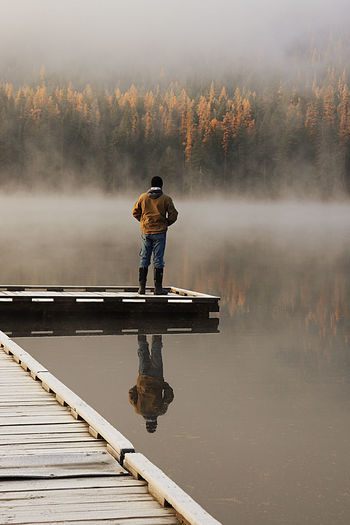 Rear view of man standing on pier at lake during foggy weather