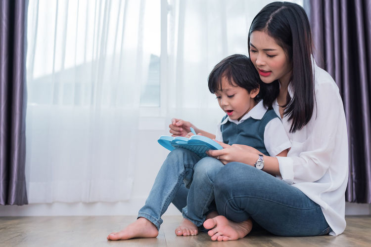 Mother Teaching Son While Sitting On Floor At Home