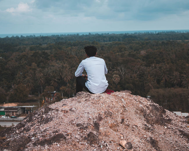 Rear view of man looking at land while sitting on rock