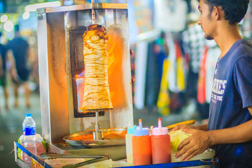 Bangkok, Thailand - March 2, 2017: Street vendor is selling grilled kebab, the popular street foods at Khao San Road night market, Bangkok, Thailand. Grilling Kebab Meat Kebabs Khao San Rd Khao San Road KhaoSan Khaosan Rd. Khaosandroad Tourist Tourist Attraction  Tourists Adult Bottle Business Casual Clothing Container Day Focus On Foreground Food Food And Drink Glass Incidental People Indoors  Jar Kebab Kebab Shop Kebabers Khao San Khao San Knok Wua Khao San Rd. Khaosan Road Khaosanroad Market Men Night Market Night Market In Thailand Night Market, One Person Real People Retail  Standing Table Tourist Destination