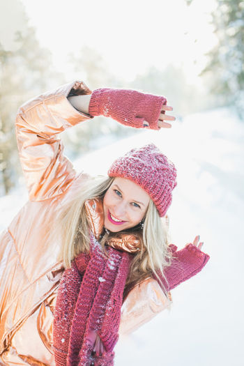 Portrait Of Happy Young Woman Enjoying By Trees On Snowy Field In Winter