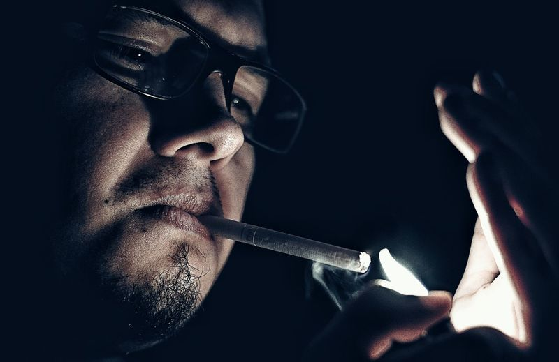Close-up of man igniting cigarette from lighter in dark