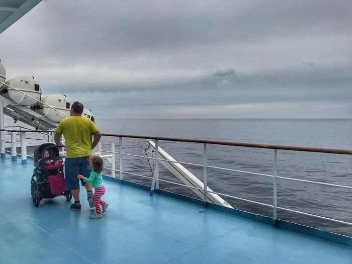 Rear View Full Length Of Father With Children In Cruise Ship At Sea