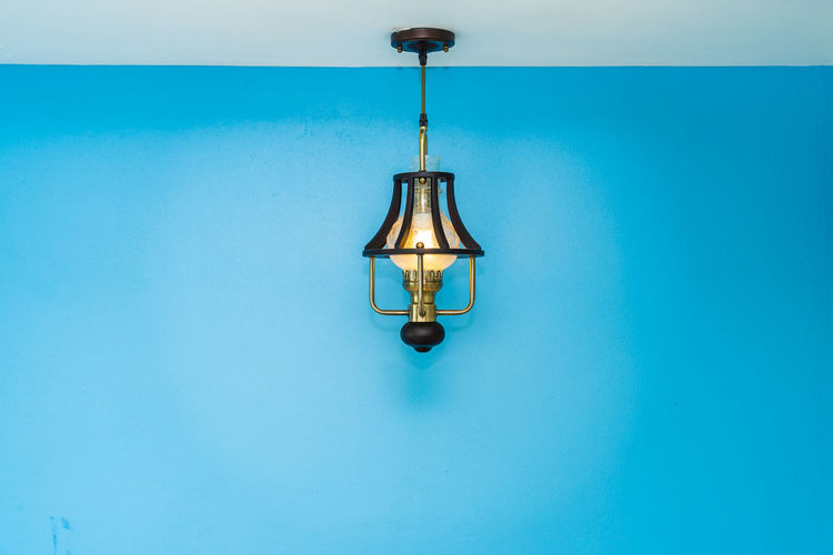 Close-up of illuminated electric lamp against blue wall