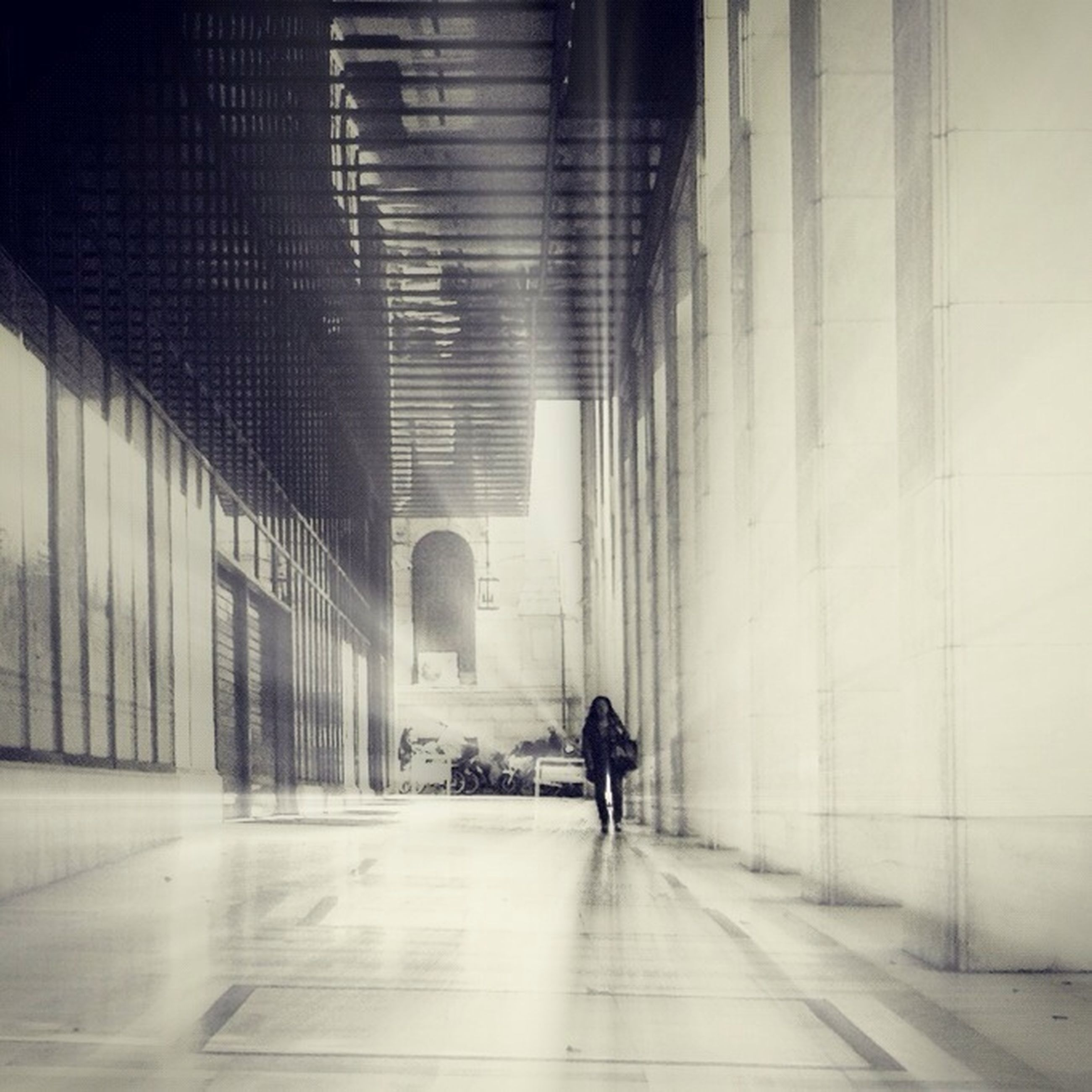 indoors, walking, full length, architecture, built structure, corridor, rear view, the way forward, men, lifestyles, tunnel, person, building, wall - building feature, wall, tiled floor, flooring, diminishing perspective