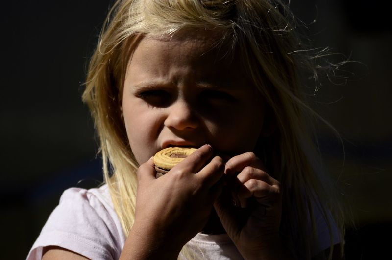 Close-up portrait of cute girl eating food against black background