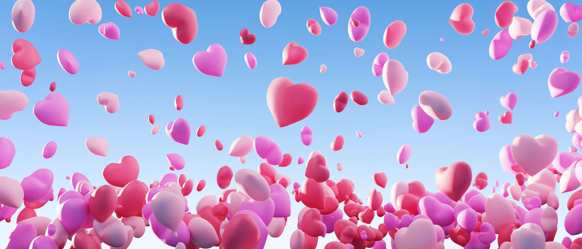 Low angle view of pink balloons flying against blue sky