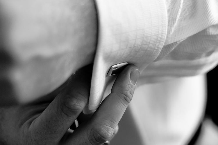 Midsection of man buttoning cuff