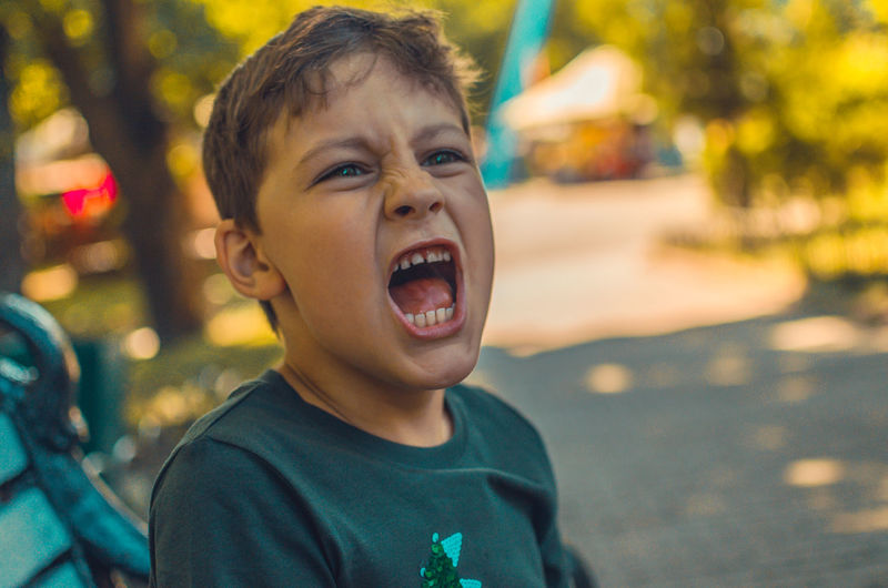Close-up of angry boy screaming in park