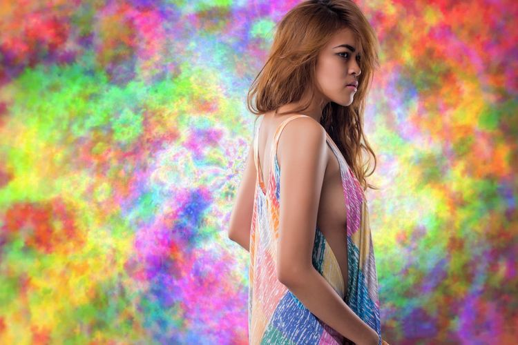 Beautiful young woman standing against multi colored wall