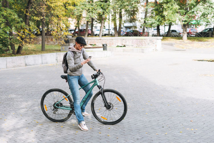 Man riding bicycle on road in city