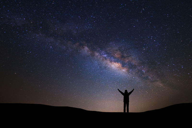 Arms Raised Astronomy Beauty In Nature Galaxy Human Arm Human Limb Leisure Activity Lifestyles Milky Way Nature Night One Person Real People Scenics - Nature Silhouette Sky Space Standing Star Star - Space Star Field Tranquil Scene Tranquility