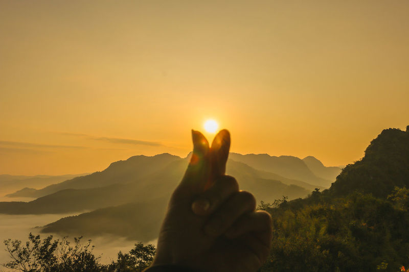 Beauty In Nature Body Part Bright Finger Hand Human Body Part Human Finger Human Hand Lens Flare Lifestyles Mountain Mountain Range Nature Non-urban Scene One Person Orange Color Outdoors Real People Scenics - Nature Sky Sun Sunset Tranquil Scene Tranquility