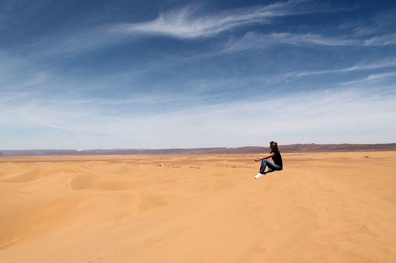 Full length of woman sitting on sand dune at sahara desert against sky