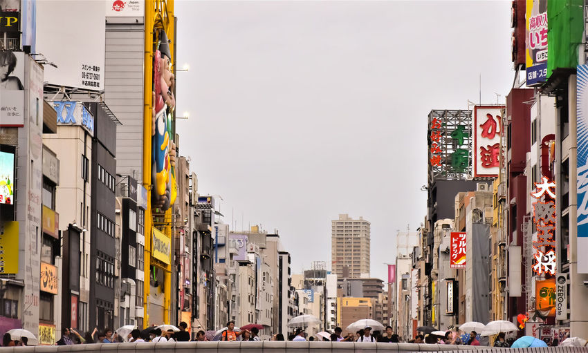 Traffic on road by buildings in city against osaka skyline in japan
