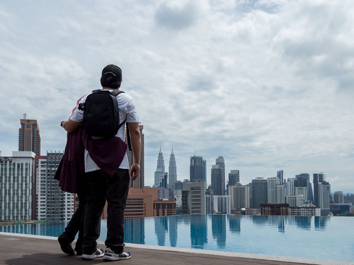 Rear view of couple standing by cityscape against sky