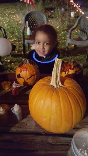 Portrait of cute girl lying on pumpkin at night