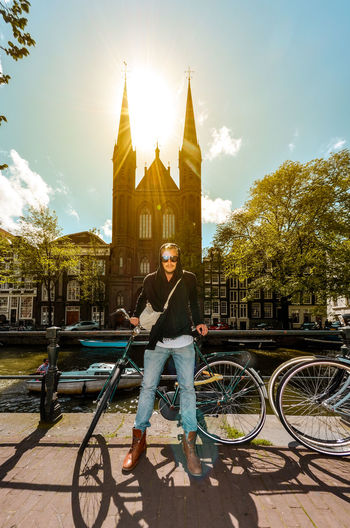 Portrait of man riding bicycle against building
