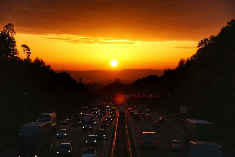 Traffic on road in city during sunset