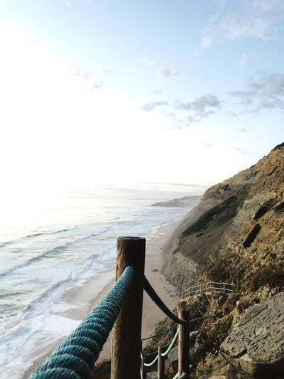 Close-up of railing on beach against sky