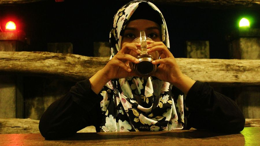 Portrait of woman in hijab having drink at table