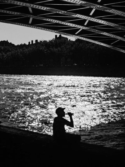 Silhouette man fishing at sea against sky