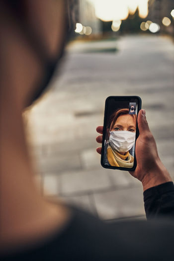 Young man having video call with her mother standing outdoors in the street in the evening