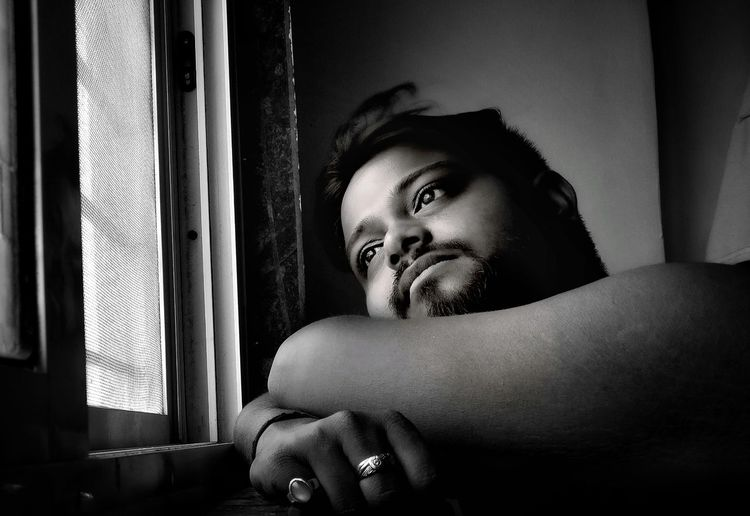 Close-Up Of Thoughtful Young Man Looking Through Window While Sitting At Home