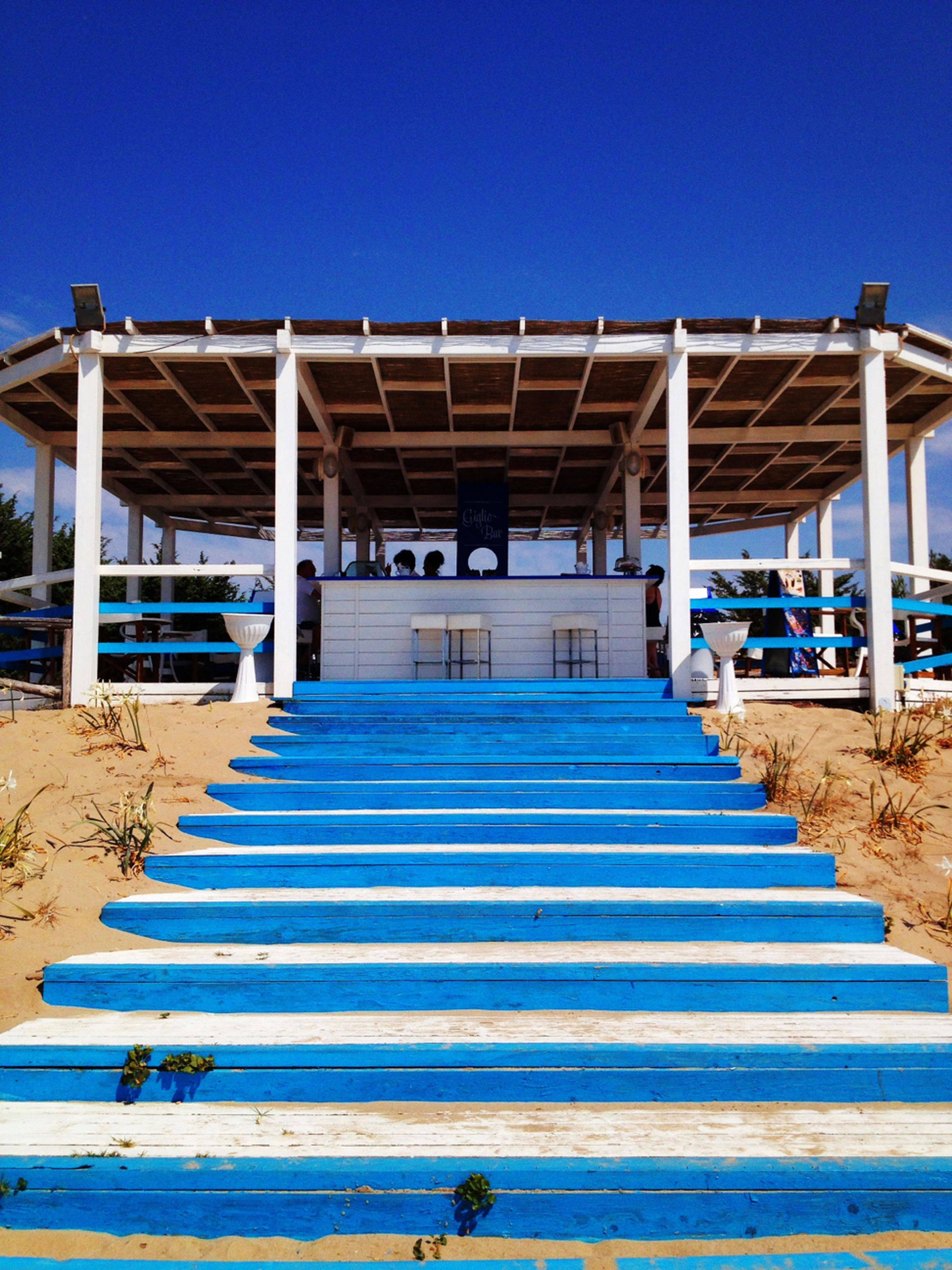 clear sky, blue, built structure, architecture, copy space, sunlight, building exterior, railing, beach, shadow, sea, the way forward, day, water, pier, sand, wood - material, sunny, outdoors, incidental people