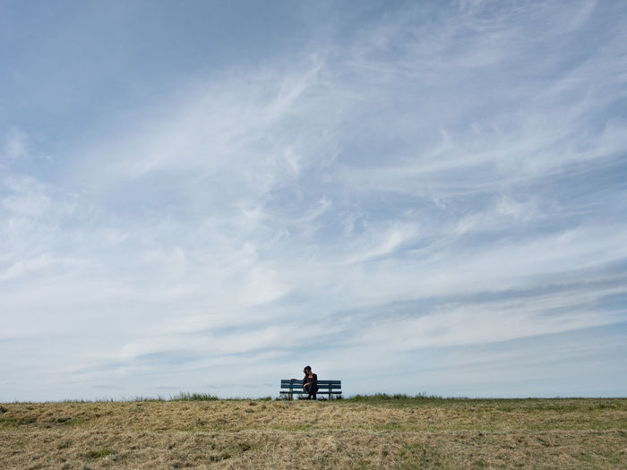 Woman sitting on bench against sky