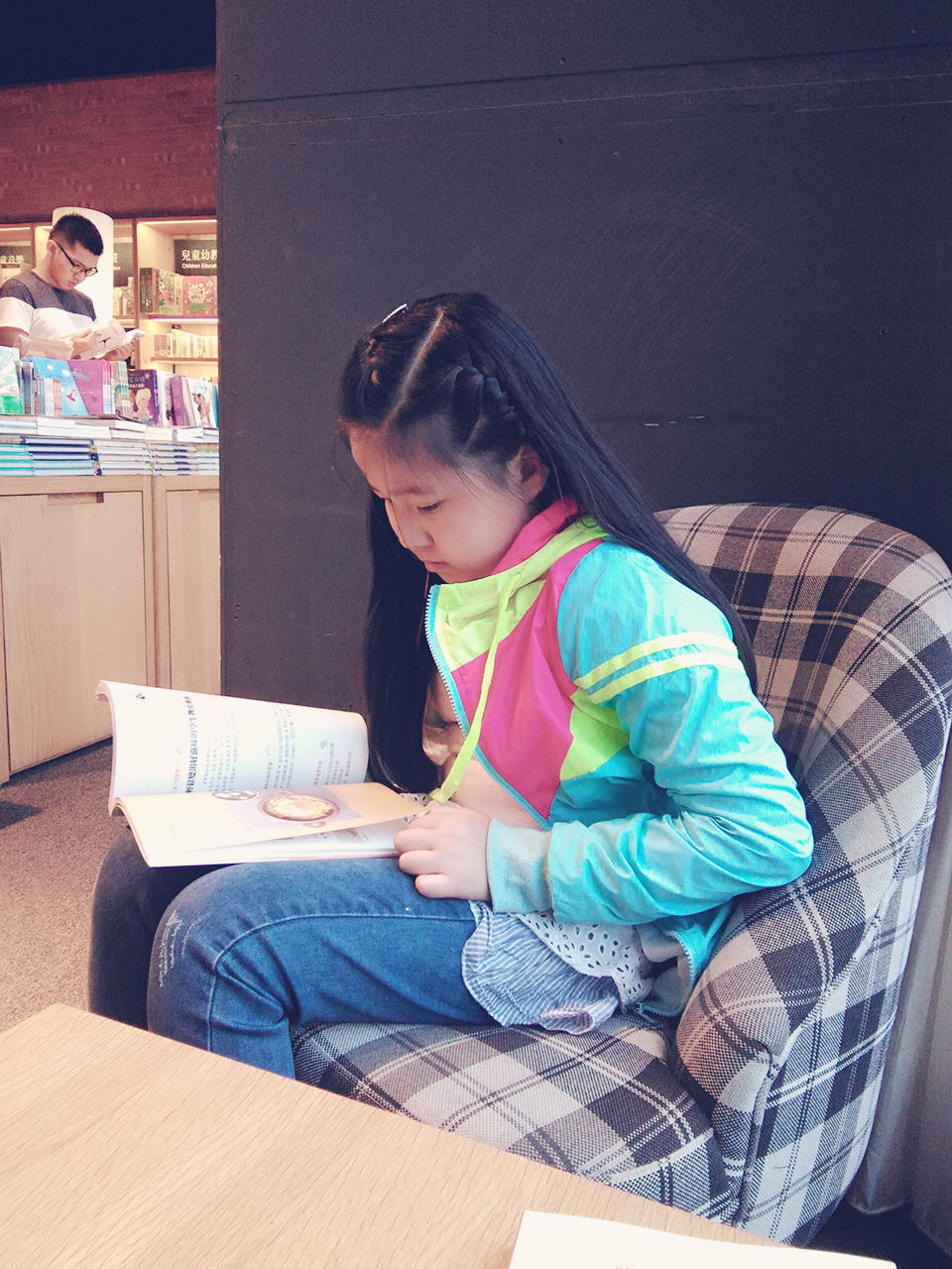 real people, sitting, technology, black hair, childhood, casual clothing, indoors, home interior, full length, one person, wireless technology, leisure activity, lifestyles, girls, day, young adult, people