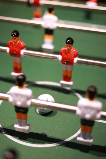 Table football game Sport Human Representation Male Likeness Leisure Games Representation Figurine  Soccer Team Sport Relaxation Competition Leisure Activity Close-up Green Color No People Cooperation Teamwork Indoors  Selective Focus Red Challenge Table Football Figure Recreation