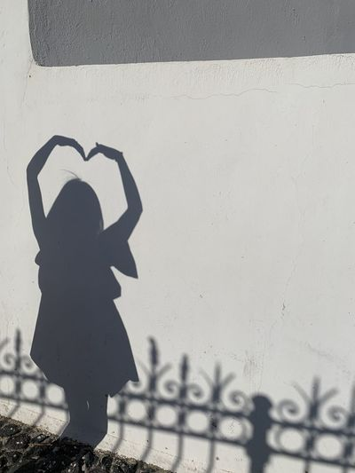 Shadow of woman standing against wall