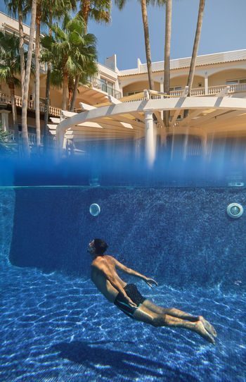 Man swimming in pool by sea