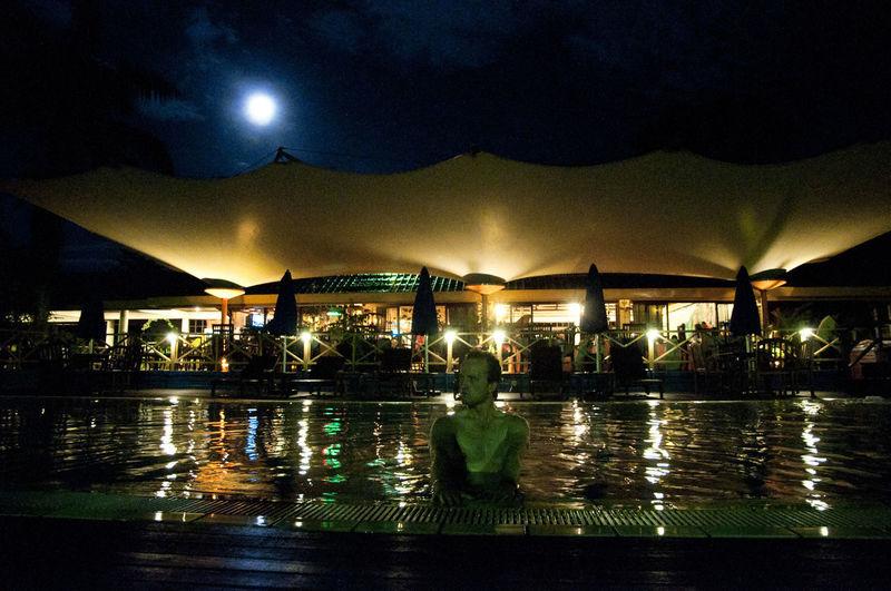 People swimming in pool at night