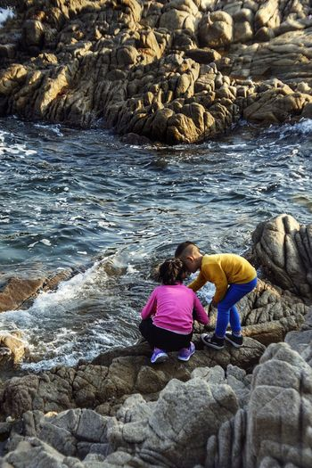 Beach Beauty In Nature Child Childhood Females Flowing Water Girls Leisure Activity Lifestyles Outdoors People Real People Rock Rock - Object Sea Sister Sitting Solid Togetherness Two People Water Women