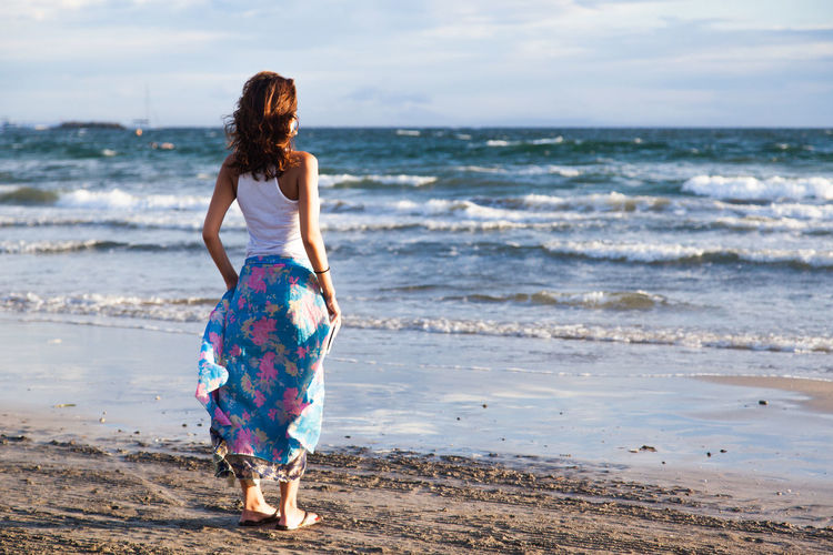 Full Length Rear View Of Woman Standing At Beach On Sunny Day