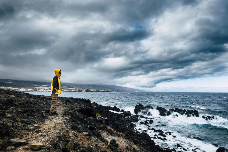 Side view of man standing at beach against cloudy sky