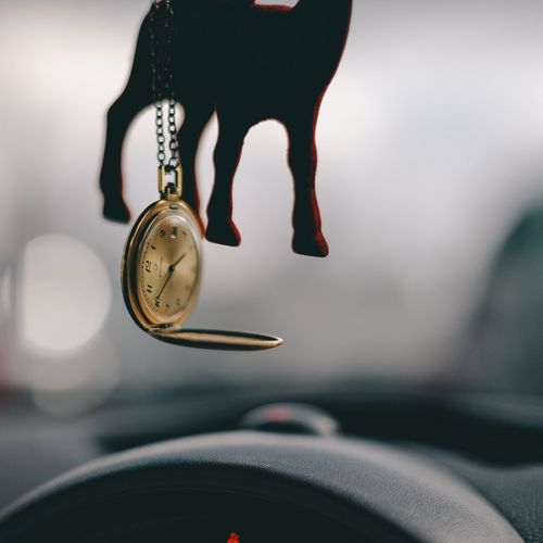 Close-up of pocket watch hanging in car