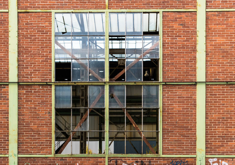 Broken Windows On Brick Wall Of Abandoned Factory