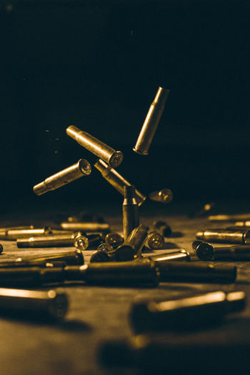 Close-Up Of Bullet Shells On Table Against Black Background