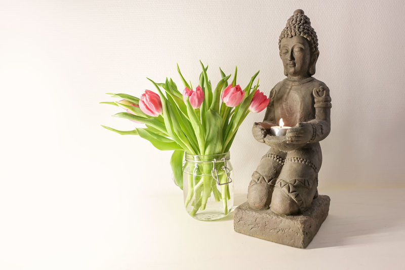 Buddha statue in vase against white wall